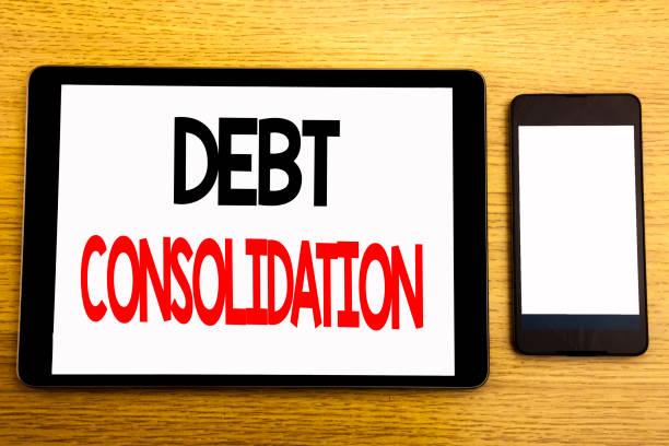 Schreiben Text zeigt Schuldenkonsolidierung. Geschäftskonzept für Geld Kredit Kredit geschrieben am Tablet Laptop, hölzernen Hintergrund mit Haftnotizen, Kaffee und Stift – Foto