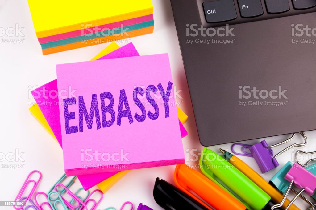 Writing text showing Embassy made in the office with surroundings such as laptop, marker, pen. Business concept for Tourist Visa Application Workshop white background copy space stock photo
