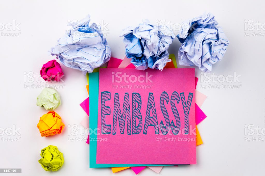 Writing text showing Embassy written on sticky note in office with screw paper balls. Business concept for Tourist Visa Application on the white isolated background. stock photo