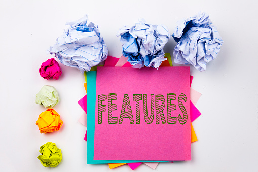 istock Writing text showing Features written on sticky note in office with screw paper balls. Business concept for Advertisement Advertising on the white isolated background. 887664674
