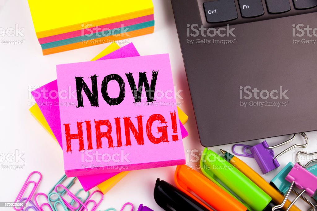 Writing text showing Now Hiring made in the office with surroundings such as laptop, marker, pen. Business concept for Recruitment and Job recruiting advertisement white background with copy space stock photo