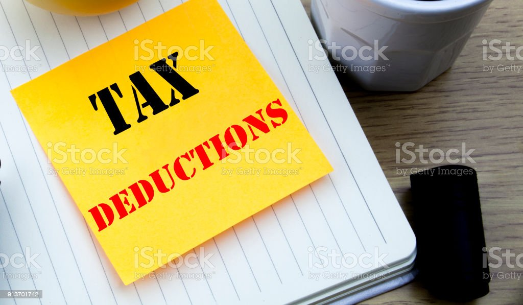 Writing text showing Tax Deductions. Business concept for Finance Incoming Tax Money Deduction written sticky note empty paper, Wooden background with copy space, Coffee and marker stock photo