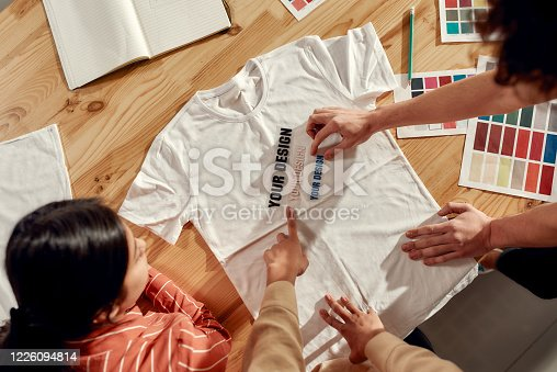 Top view of creative people trying on stickers with text, while discussing logo and design of T-shirt. Young man and women working together at custom T-shirt, clothing printing company. Cropped shot