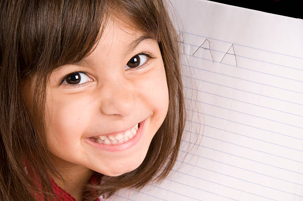 Writing the Letter A Young child has written capital A on notebook paper. illiteracy stock pictures, royalty-free photos & images