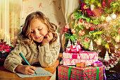 Beautiful little girl writing a letter to Santa near Christmas tree