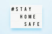 STAY HOME SAFE written in light box on blue background. Healthcare and medical concept. Top view, copy space. Quarantine concept.