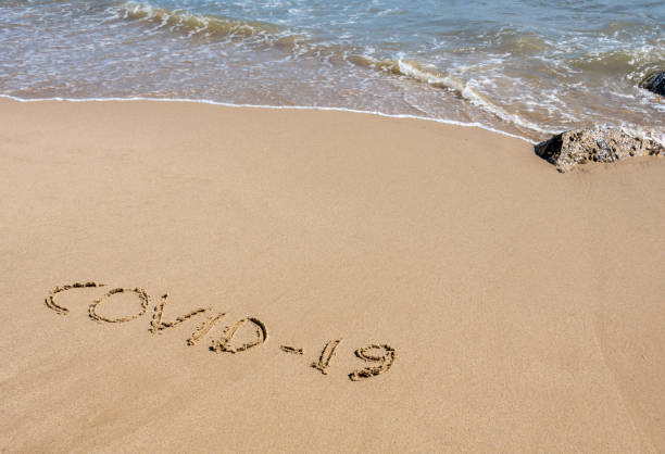 COVID-19 written in sand on a beach with the sea stock photo