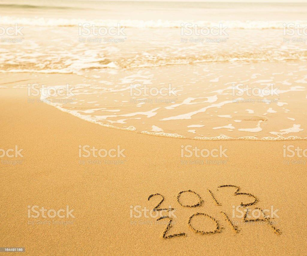 2013 - 2014 written in sand on beach texture stock photo