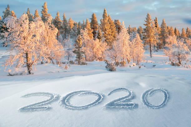 2020 geschrieben im Schnee, Berglandschaft im Hintergrund, Urlaubsgrußkarte – Foto
