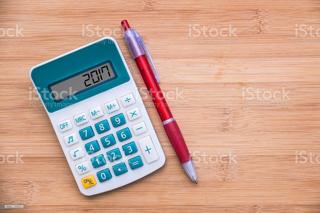 2017 written on a calculator and a pen on wood stock photo