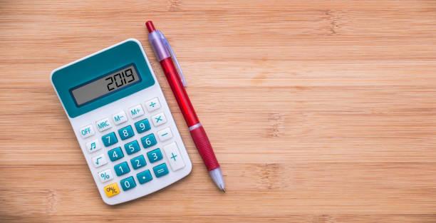 2019 auf einen Taschenrechner und einen Stift auf hölzernen Hintergrund geschrieben – Foto