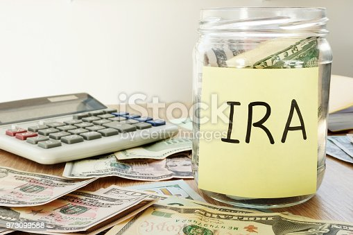 IRA written on a stick and jar with dollars.