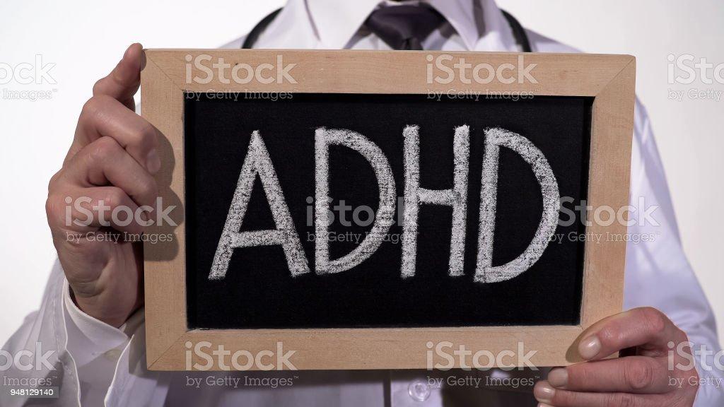 ADHD written on blackboard in therapist hands, psychiatric mental disorder stock photo