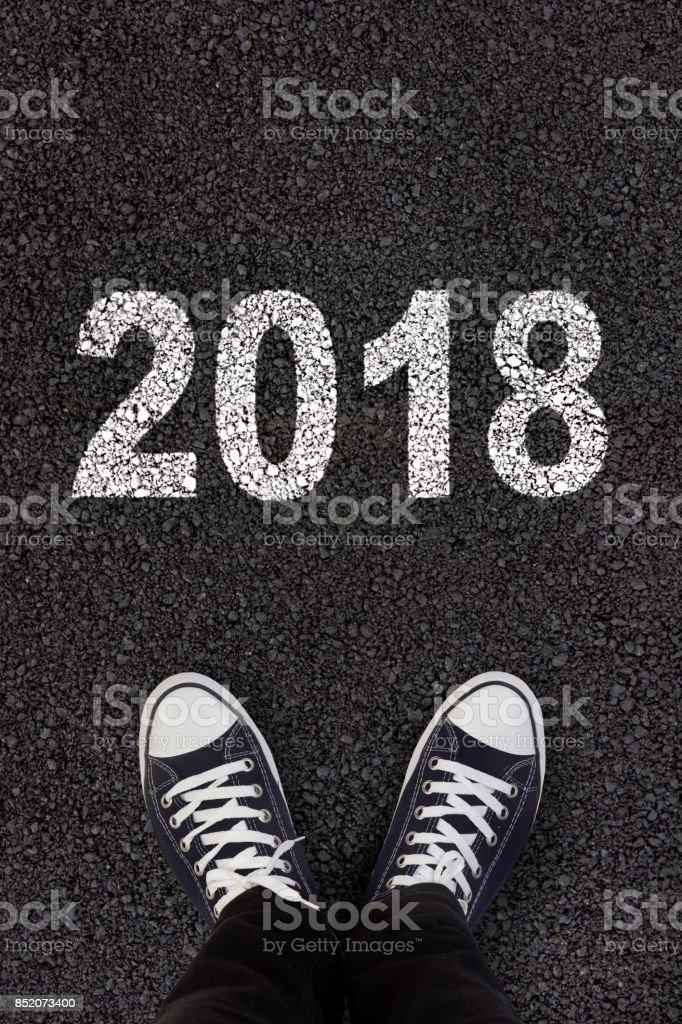 2018 written on fresh asphalt with man's feet stock photo