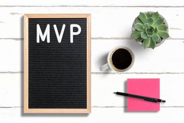 MVP auf Brieftafel neben Haftnote, Kaffee und einer saftigen Pflanze geschrieben – Foto