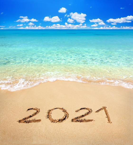 2021 written on sandy beach stock photo