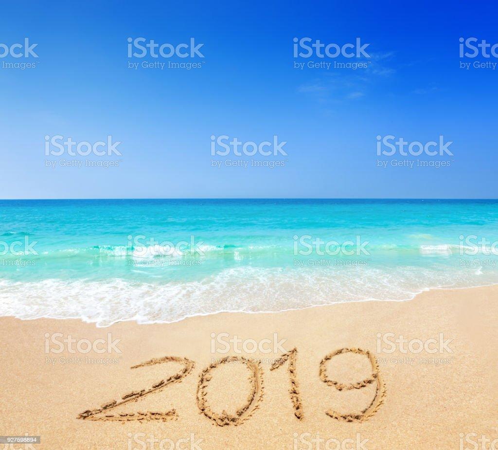 2019 written on sandy beach stock photo