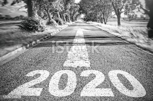 1150191246 istock photo 2020 written on the asphalt. An arrow shows the way forward 1209204929