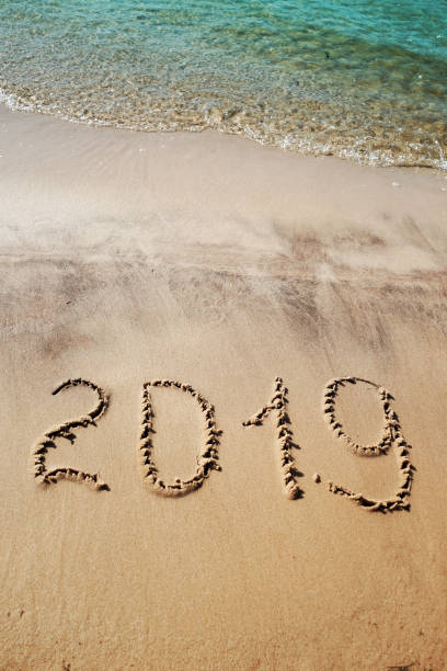 2019 written on the beach sand. aquamarine sea waves. concept for new year, christmas greetings, postcards, flyers, posters. natural texture. vertical image - number 19 stock photos and pictures