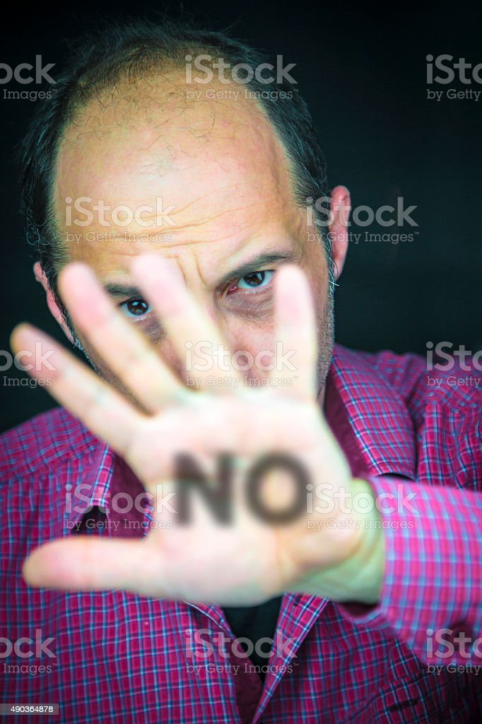 NO written on the palm of a man's hand stock photo