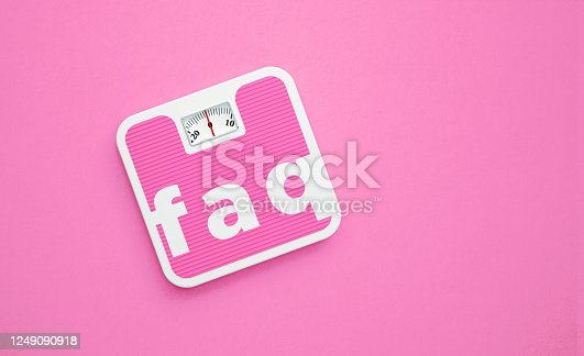 FAQ written pink weight scale on pink  background. Horizontal composition with copy space. Directly above.