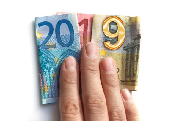 2019 geschrieben mit Euro-Banknoten in eine Hand, die isoliert auf weißem Hintergrund – Foto