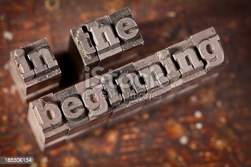INT THE BEGINNING Written In Old Grungy Metal Typeset On Wooden Background