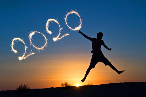 2020 parıltıları ile yazılmış, güneşte atlama bir çocuğun silueti, tatil kartı - sembolizm akımı stok fotoğraflar ve resimler