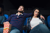 Young man watching a movie at the cinema, while his girlfriend using her smart phone and getting bored.