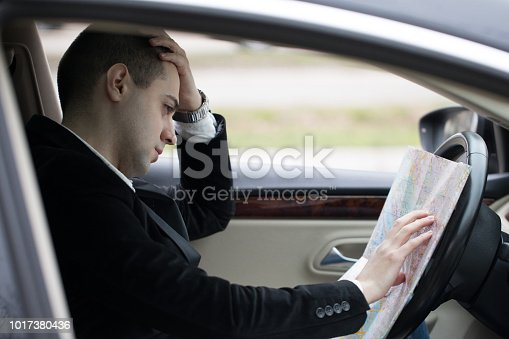 Man driving a car and searching for directions