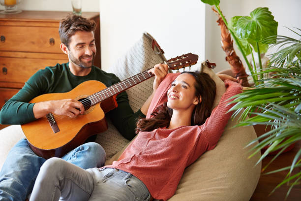 I wrote this just for you Shot of a young man playing guitar for his girlfriend while relaxing in their living room serenading stock pictures, royalty-free photos & images