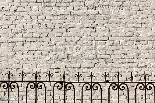 Vintage openwork forged fence on the background of the light brick wall of the house
