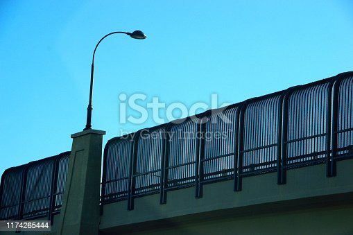 A wrought iron decorative street lamp on a bridge against the backdrop of bright, clear, blue, summer sky. Copy space.