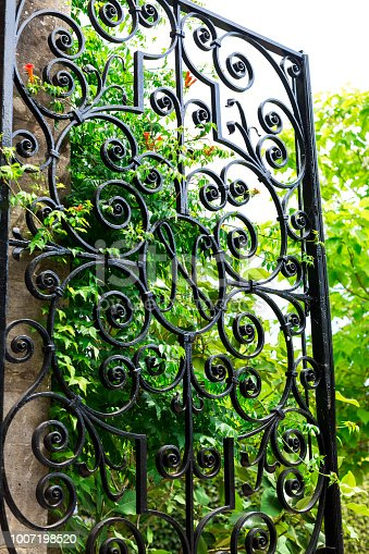 Vertical color image depicting a black wrought iron garden gate with lush green foliage beyond the gate. The gate is open, providing an invitation into the garden. Room for copy space.