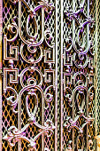 Wrought iron gate with intricate patterns, seen along a local street. Night time photography where the gate is lit by nearby mixed lighting.