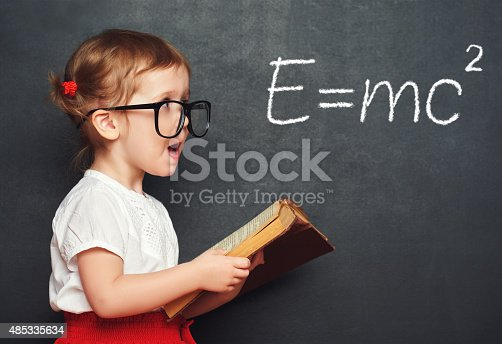 istock wunderkind little girl schoolgirl with a book from the blackboar 485335634