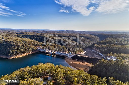 Warragamba dam of Sydney Water supply infrastructure on Nepean river forming fresh water lake between gum-tree woods. Aerial view over dam wall, bridge, gate and surrounding area.