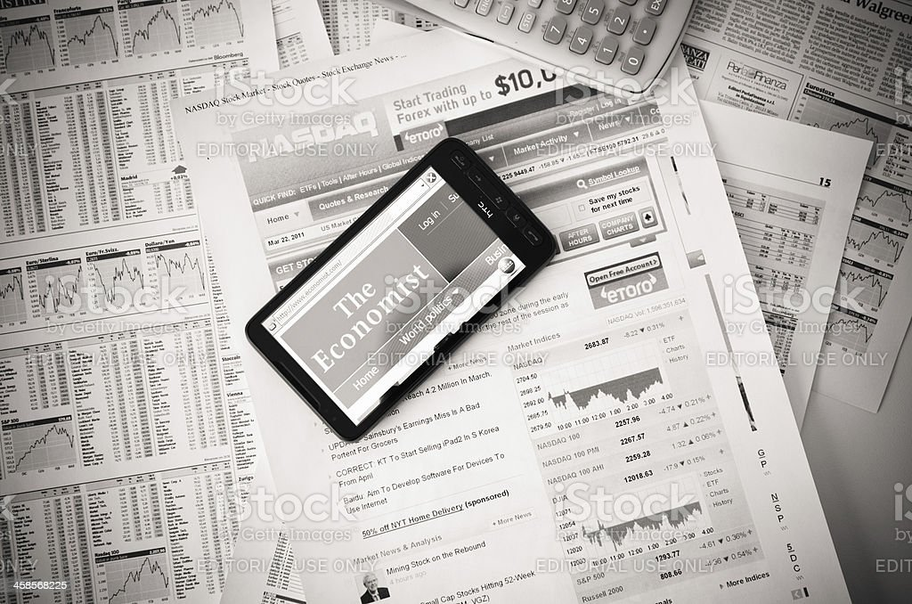 www.economist.com on HTC smart phone and financial newspaper royalty-free stock photo
