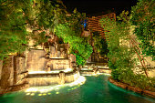 Las Vegas, Nevada, United States - August 18, 2018: Wynn Las Vegas Waterfall Fountain. The Wynn is Resort Hotel 5-star casino in Las Vegas Strip. Falls in the garden outdoors illuminated by night.