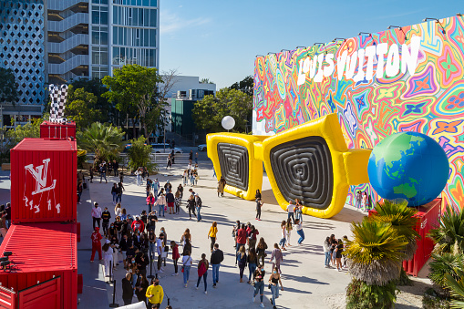 Wynwood, Miami Beach, Florida, USA - December 27, 2020: General landscape view of Louis Vuitton's pop up shops. Nationals and internationals tourists enjoying a warm blue day at Miami Design District - Wynwood, visiting and walking around the Louis Vuitton's containers.\n\nWynwood is a former industrial district of Miami, redeveloped with colorful murals that cover the walls of many of the buildings. In those days, the visitors can find here the most fancy and expensive cafes, restaurants and shops.