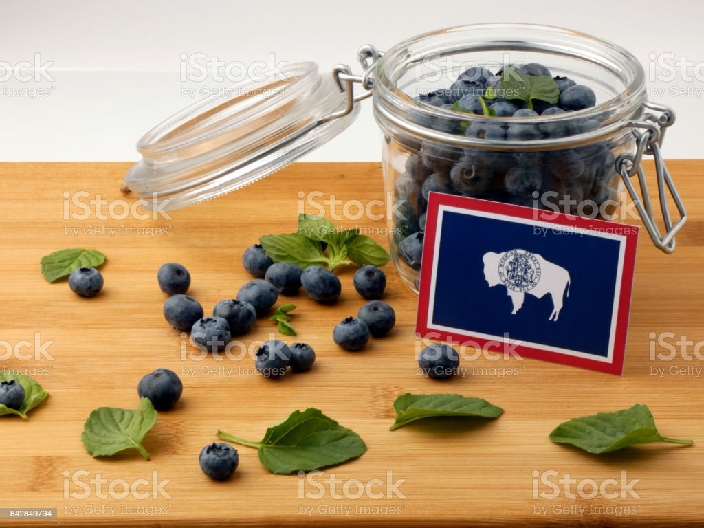 Wyoming flag on a wooden plank with blueberries isolated on white stock photo