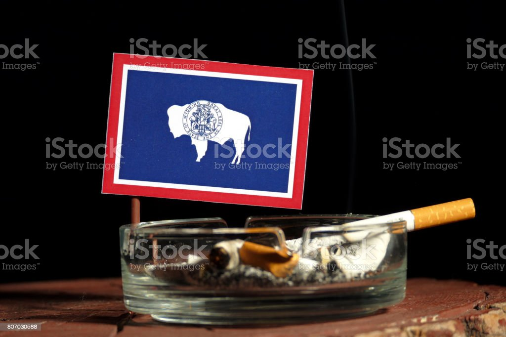 Wyoming flag with burning cigarette in ashtray isolated on black background stock photo