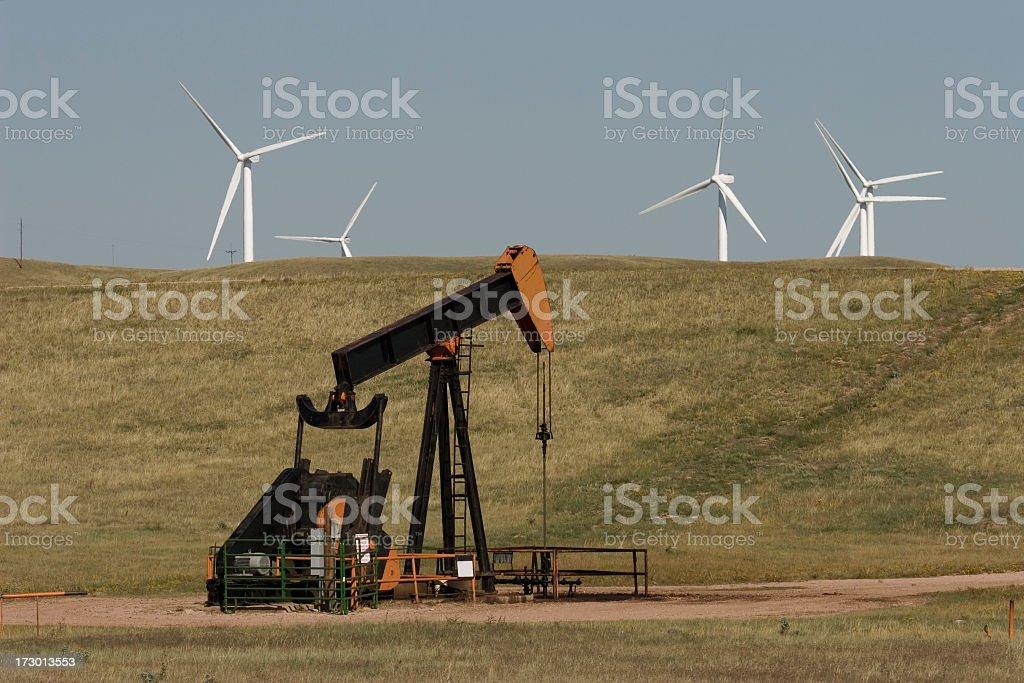 Wyoming oil pump jack and renewable wind turbines on prairie stock photo