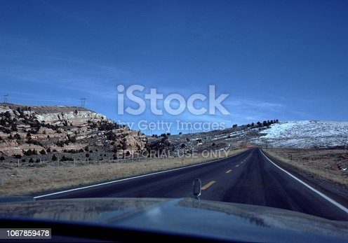 Wyoming, United States - January 01, 1976:  Car point of view from front windshield down a two lane highway among badlands of Wyoming, United States, with road receding to a vanishing point among snow-covered hills, during a road trip, 1976