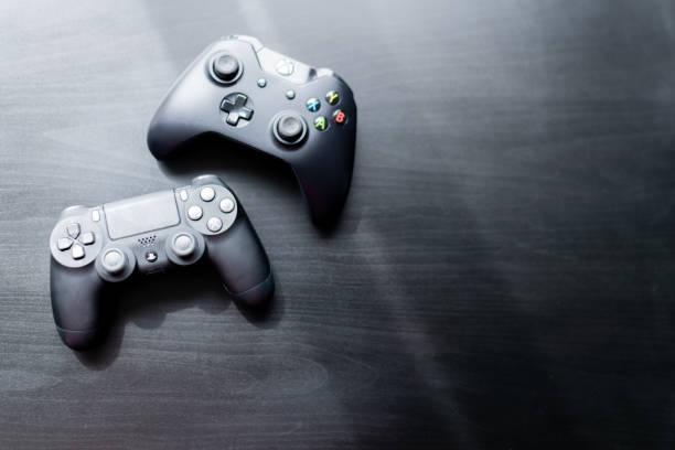 xbox en playstation controller zat naast elkaar op een donkere achtergrond - playstation stockfoto's en -beelden