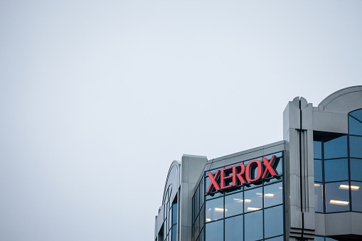 Picture of a sign with the logo of Xerox in front of their main office in montreal, Quebec. Xerox Corporation  is an American global corporation that sells print and digital document solutions, and document technology products, famous for its photocopiers