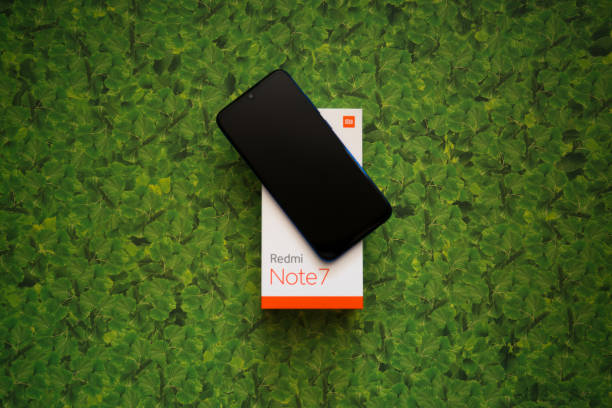 Xiaomi Redmi Note 7 smartphone on green leaves background stock photo