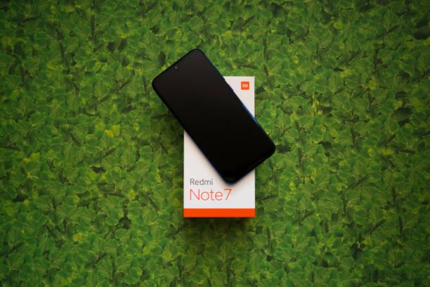 Xiaomi Redmi Note 7 Smartphone auf grüner Blätterbackground – Foto