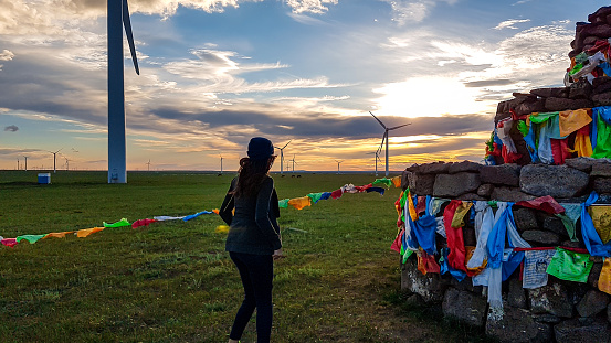 A woman in beanie walking around a heap of stones (Aobao) build on a vast pasture in Xilinhot in Inner Mongolia. The heap has colorful prayer flags attached to it. The sun is setting. Wind turbines
