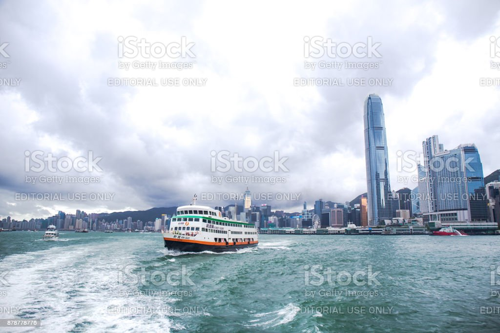Xin Guo ferry ship of New World First Ferry Services depart from Central ferry pier Hong Kong island in cloudy day stock photo